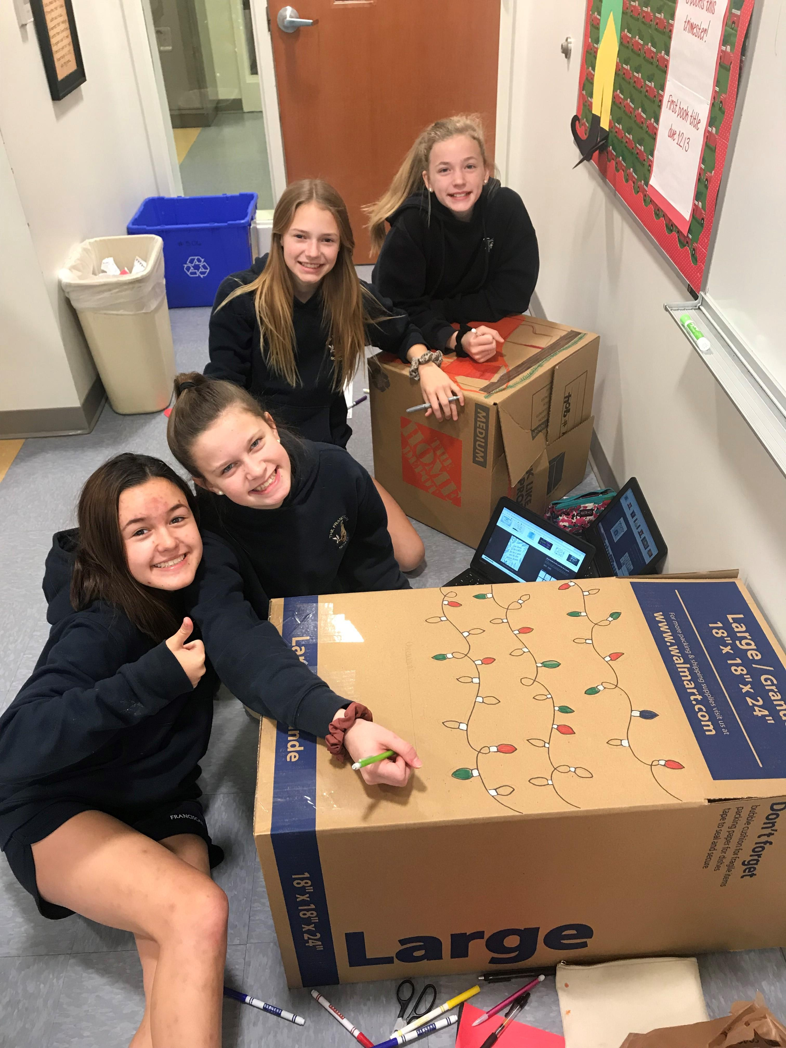 Students are decorating boxes that went to the class' adopted family during the holidays.